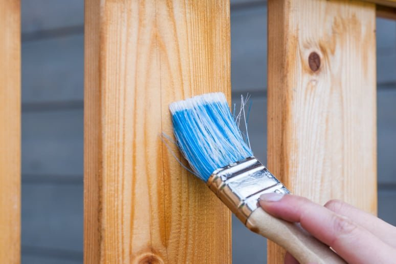 close up of a wooden fence being stained by a paint brush held by a man