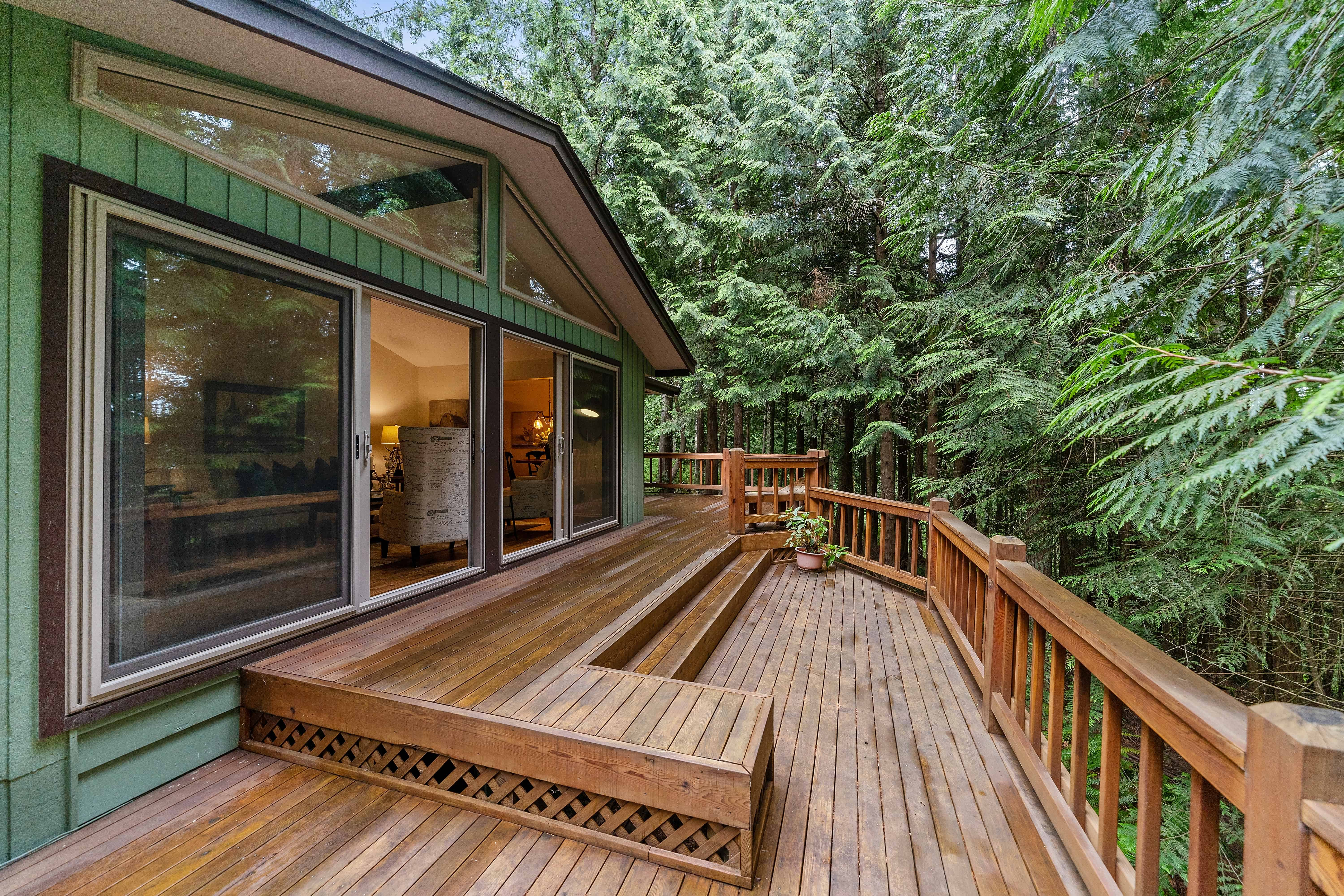 brown stained deck surrounded by green trees attached to a home with large windows