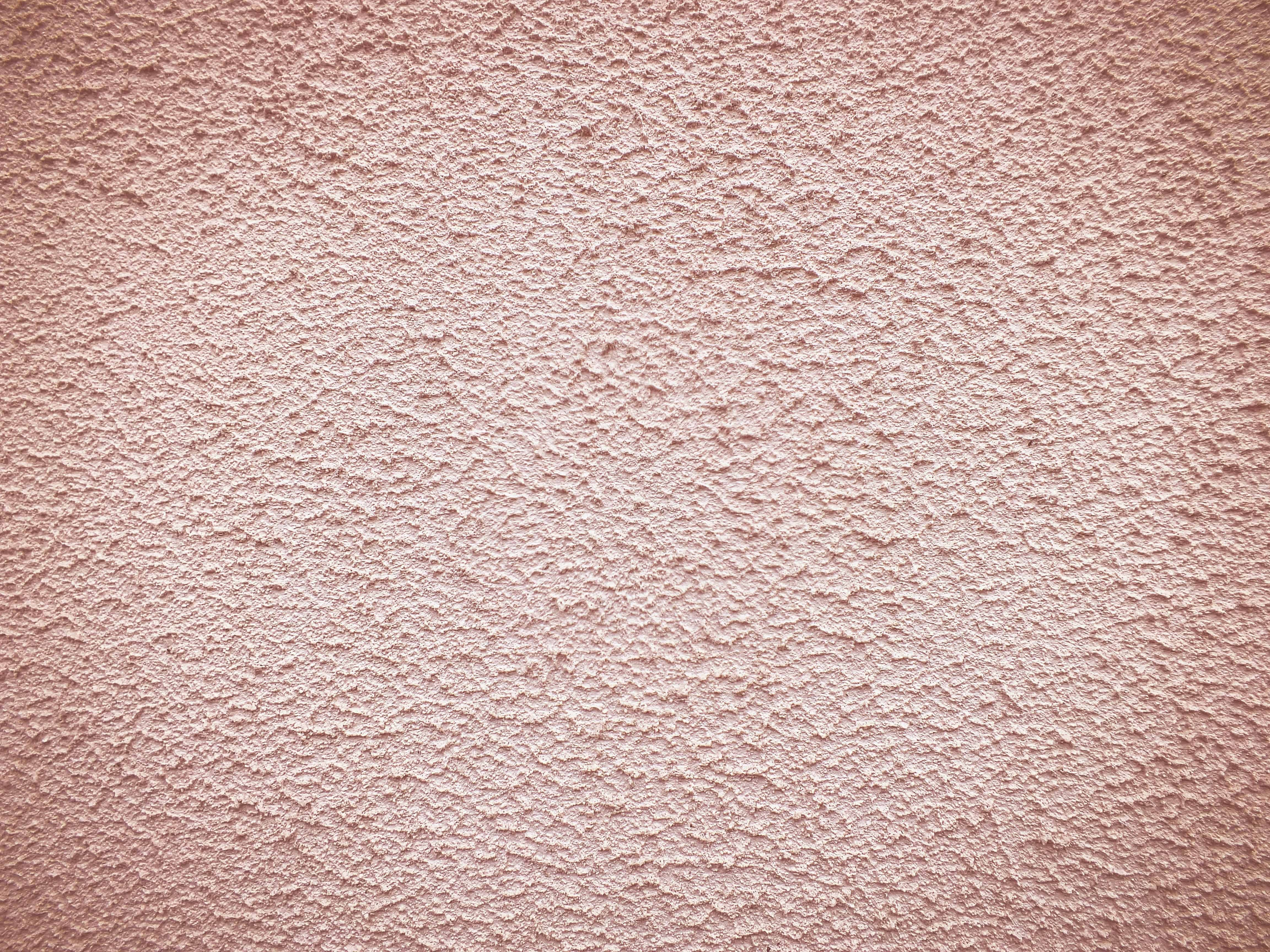 a close up of a pink stucco wall